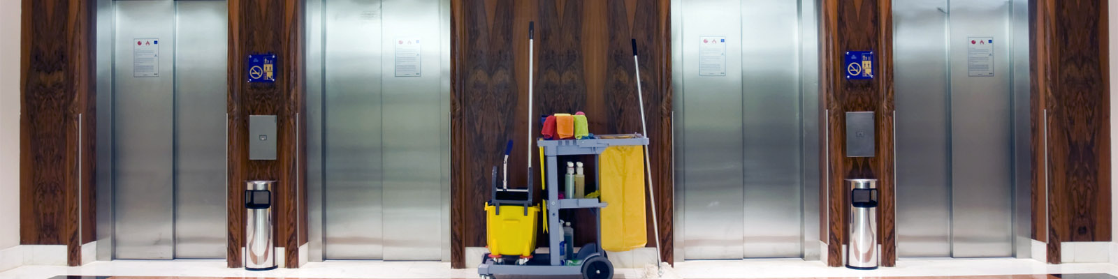 A commercial cleaning services cart in front of elevators.