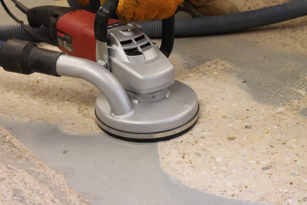 A contractor grinding a concrete floor.