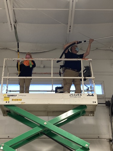 Industrial cleaning services in action, cleaning rafters.
